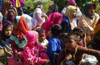 Rohingya refugees, who landed on an isolated northern shore near the Malaysia-Thai border, huddle in a group in Kangar on March 1, 2019, following their detention by Malaysian immigration authorities. - Thirty-four Rohingya landed on an isolated beach in Malaysia on March 1, police said, the first group of the Muslim minority caught arriving in the country by sea for almost a year. (Photo by ISMAEL KAMALDIN / AFP)