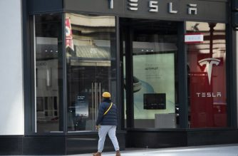 "A man walks past a Tesla store in Washington, DC on March 4, 2019. - Tesla is planning to unveil a new electric ""crossover"" vehicle March 14 which is slightly bigger and more expensive than its most affordable model, according to chief executive Elon Musk. The news comes shortly after Tesla unveiled its lowest-priced Model 3, an electric car designed for the masses, at a base price of $35,000, with deliveries promised within one month. (Photo by Andrew CABALLERO-REYNOLDS / AFP)"