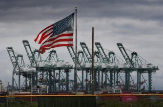 The US flag flies over shipping cranes and containers after a report said the United States and China are close to reaching a major trade deal that would see both sides lower some of the tariffs imposed during an often-bitter trade war, in Long Beach, California on March 4, 2019. (Photo by Mark RALSTON / AFP)