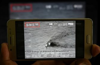 A Pakistani journalist watches a video released by Pakistan's Navy that allegedly shows an Indian submarine, on a smartphone in Islamabad on March 5, 2019. - Pakistan has stopped an Indian submarine from entering its waters, the navy said on March 5, as tensions continue to run high between the nuclear-armed foes. The navy released what it said was video of the submarine, with the grainy black and white footage showing only what appeared to be a periscope above water. The timestamp on the video clip shows it began at 8.35 pm on March 4. (Photo by AAMIR QURESHI / AFP)
