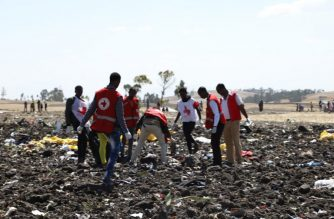 Red cross team work amid debris at the crash site of Ethiopia Airlines near Bishoftu, a town some 60 kilometres southeast of Addis Ababa, Ethiopia, on March 10, 2019. - An Ethiopian Airlines Boeing 737 crashed on March 10 morning en route from Addis Ababa to Nairobi with 149 passengers and eight crew believed to be on board, Ethiopian Airlines said. (Photo by Michael TEWELDE / AFP)