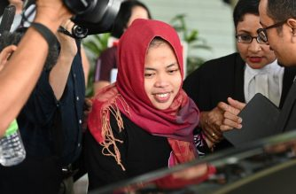 Indonesian national Siti Aisyah (C) smiles while leaving the Shah Alam High Court, outside Kuala Lumpur on March 11, 2019 after her trial for her alleged role in the assassination of Kim Jong Nam, the half-brother of North Korean leader Kim Jong Un. - An Indonesian woman accused of assassinating the North Korean leader's half-brother was to be freed March 11 after a prosecutor withdrew a murder charge against her, a judge said. (Photo by MOHD RASFAN / AFP)