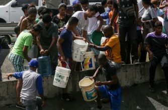 """People collect water from a broken pipe, flowing into a sewage canal at the Guaire river in Caracas on March 11, 2019, as a massive power outage continues affecting some areas of the country. - Venezuela's opposition leader Juan Guaido will ask lawmakers on Monday to declare a """"state of alarm"""" over the country's devastating blackout in order to facilitate the delivery of international aid -- a chance to score points in his power struggle with President Nicolas Maduro. (Photo by Cristian HERNANDEZ / AFP) / """"The erroneous mention[s] appearing in the metadata of this photo by Cristian HERNANDEZ has been modified in AFP systems in the following manner: [collect water from a broken pipe, flowing into a sewage canal at the Guaire river ] instead of [collect water from a sewage canal at the river Guaire ]. Please immediately remove the erroneous mention[s] from all your online services and delete it (them) from your servers. If you have been authorized by AFP to distribute it (them) to third parties, please ensure that the same actions are carried out by them. Failure to promptly comply with these instructions will entail liability on your part for any continued or post notification usage. Therefore we thank you very much for all your attention and prompt action. We are sorry for the inconvenience this notification may cause and remain at your disposal for any further information you may require."""""""