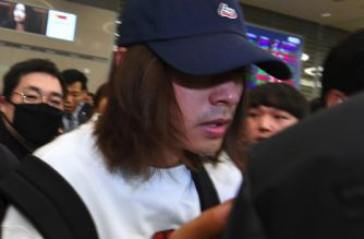 This picture taken on March 12, 2019 shows K-pop star Jung Joon-young (C) surrounded by reporters as he arrives at Incheon international airport in Incheon. - A burgeoning K-pop sex scandal claimed a second scalp as a singer who rose to fame after coming second in one of South Korea's top talent shows admitted secretly filming himself having sex and sharing the footage. Jung Joon-young, 30, announced his immediate retirement from showbusiness amid allegations he shot and shared sexual imagery without his partners' consent. (Photo by - / YONHAP / AFP) / - South Korea OUT / REPUBLIC OF KOREA OUT  NO ARCHIVES  RESTRICTED TO SUBSCRIPTION USE