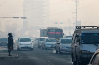 This picture taken on February 14, 2019 shows vehicles commuting along a road on a polluted day in Ulaanbaatar, the capital of Mongolia. - In the world's coldest capital, many burn coal and plastic just to survive temperatures as low as minus 40 degrees -- but warmth comes at a price: deadly pollution makes Ulaanbataar air too toxic for children to breathe, leaving parents little choice but to evacuate them to the countryside. (Photo by BYAMBASUREN BYAMBA-OCHIR / AFP) / TO GO WITH AFP STORY ASIA-CLIMATE-POLLUTION-MONGOLIA-HEALTH-CHILDREN,FEATURE BY KHALIUN BAYARTSOGT