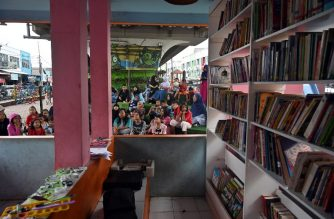 "This photo taken in Tangerang, Banten province on February 10, 2019 shows children attending a program at the under bridge libraby called ""TBM Kolong"". - Singing and laughter briefly drowns out the roar of motors under a Jakarta flyover that has become an unlikely haven for book lovers. Some 50 children have gathered at this tiny open air library wedged between two lanes of traffic outside Indonesia's capital, a city of more than 10 million people notorious for its hours-long traffic jams. (Photo by ADEK BERRY / AFP) / TO GO WITH: Indonesia-education, FOCUS by Harry PEARL"