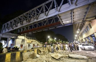 Onlookers and rescue workers gather at the site of a footbridge after its collapse, outside the Chhatrapati Shivaji Maharaj Terminus railway complex in Mumbai, on March 14, 2019. - Four people were killed and dozens injured when a footbridge collapsed near Mumbai's main train station on March 14, 2019, the latest accident to highlight creaking infrastructure in India's financial capital. (Photo by - / AFP)