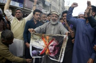 Pakistan traders burn a poster with the image of Brenton Tarrant, the man charged in relation against the March 15 attack on two mosques in Christchurch, during a protest in Peshawar on March 16, 2019. - A right-wing extremist armed with semi-automatic weapons rampaged through two mosques in the quiet New Zealand city of Christchurch during afternoon prayers on March 15, killing 49 worshippers and wounding dozens more. (Photo by ABDUL MAJEED / AFP)