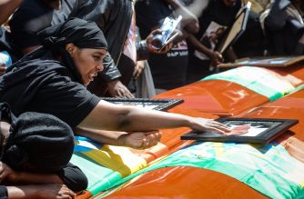 A mourner of victims of the crashed accident of Ethiopian Airlines touches a portrait on a coffin during the mass funeral at Holy Trinity Cathedral in Addis Ababa, Ethiopia, on March 17, 2019. - The crash of Flight ET 302 minutes into its flight to Nairobi on March 10 killed 157 people onboard and caused the worldwide grounding of the Boeing 737 MAX 8 aircraft model involved in the disaster. (Photo by Samuel HABTAB / AFP)