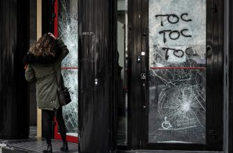 """A woman stands in front of the broken window of bank facility in Paris, on March 18, 2019, two days after protesters clashed with riot police forces on the Champs-Elysees during the 18th consecutive Saturday of demonstrations called by the 'Yellow Vest' (gilets jaunes) movement. - The """"Yellow Vests"""" protesters in France originally started as a protest about planned fuel hikes but has morphed into a mass protest against President's policies and top-down style of governing. (Photo by Philippe LOPEZ / AFP)"""