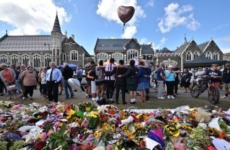 A group of students (C) sings in front of flowers left in tribute to victims at the Botanical Garden in Christchurch on March 19, 2019, four days after a shooting incident at two mosques that claimed the lives of 50 people. - New Zealanders have begun handing in weapons in response to government appeals following the Christchurch massacre, but the gesture has put some squarely in the social media firing line. (Photo by Anthony WALLACE / AFP)