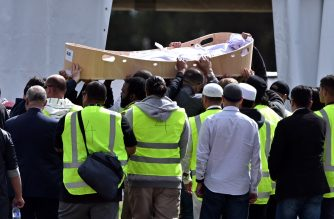 Mourners carry the first coffin of the Christchurch mosques massacre victim at Memorial Park Cemetery during the funeral ceremony in Christchurch on March 20, 2019. - As the first bodies of the Christchurch mosque shooting victims were returned to grieving families, Muslim volunteers from across New Zealand and Australia descended on the small town to help in the burial process. Islamic custom dictates that people have to be buried as soon as possible, but the scale and devastation of March 15's massacre -- that saw 50 killed in the usually quiet southern New Zealand city -- has delayed the handover of bodies to next of kin. (Photo by Anthony WALLACE / AFP)