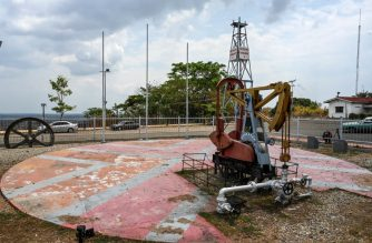 """(FILES) This file photo taken on March 15, 2019 shows a view of the """"Zumaque I"""" pumpjack with which production was started in 1914 in Mene Grande, Zulia state, Venezuela. - The modest Venezuelan town where the country's oil exploration began, attracting thousands during its boom more than a century ago, now remains impoverished and desolated, and the oil workers who used to """"live like kings"""" now struggle to survive. (Photo by Juan BARRETO / AFP)"""