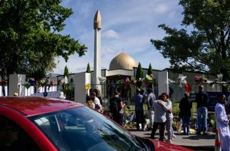 People gather outside the Al Noor Mosque after the main road that runs alongside it was opened to traffic in Christchurch on March 23, 2019. - Muslims prayed at Christchurch's main mosque for the first time since a white supremacist massacred worshippers there as New Zealand sought to return to normality after the tragedy. (Photo by Anthony WALLACE / AFP)