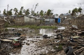 Flood water covers the ground  between rubble where there once use to be houses at an informal settlement in Beira, the fourth largest city in Mozambique, on March 23, 2019. - The man lost his house in Cyclone Idai and he has been rebuilding it the past week. The UN is stepping up calls for help in Mozambique as aid agencies struggle to assist tens of thousands of people battered by one of southern Africa's most powerful cyclones. A week after Tropical Cyclone Idai lashed Mozambique with winds of nearly 200 kilometres (120 miles) per hour, survivors are struggling in desperate conditions -- some still trapped on roof tops and those saved needing food and facing the risk of outbreaks of disease such as cholera. (Photo by WIKUS DE WET / AFP)