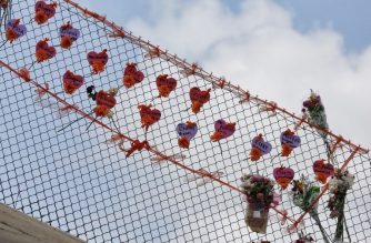 (FILES) In this file photo taken on February 21, 2018 memorials are seen on a fence surrounding Marjory Stoneman Douglas High School in Parkland, Florida. - The community of Parkland was grieving on March 25, 2019 after a second student took their life a little over a year after the shooting at the Florida town's high school which left 17 people dead. As Parkland was mourning, the authorities said the father of a child killed in the 2012 massacre at Sandy Hook Elementary School in Newtown, Connecticut, had apparently committed suicide.Jeremy Richman, 49, lost his six-year-old daughter, Avielle, in the Sandy Hook shooting which left 20 children and six staff members dead. (Photo by RHONA WISE / AFP)