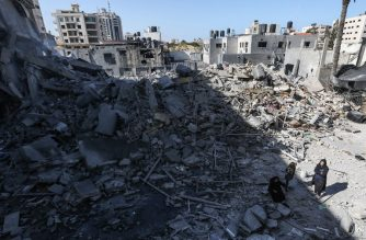 A picture taken on March 26, 2019, shows Palestinians gathering next to the rubble of a building in Gaza City, after Israeli air strikes hit dozens of sites across the Strip overnight in response to rocket fire from the Palestinian enclave. - Those strikes were in response to a rare long-distance rocket attack from the Palestinian enclave that hit a home north of Tel Aviv and wounded seven people early on Monday. (Photo by MAHMUD HAMS / AFP)