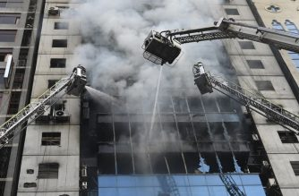 Bangladeshi firefighters on ladders work to extinguish a blaze in an office building in Dhaka on March 28, 2019. - A huge fire tore through a Dhaka office block March 28 killing at least five people with many others feared trapped in the latest major inferno to hit the Bangladesh capital. (Photo by MUNIR UZ ZAMAN / AFP)