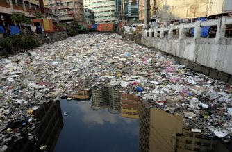 Buildings are reflected in the waters of a garbage filled river in Manila on January 23, 2016. Plastic rubbish will outweigh fish in the oceans by 2050 unless the world takes drastic action to recycle the material, a report warned January 19, on the opening day of the annual gathering of the rich and powerful in the snow-clad Swiss ski resort of Davos. AFP PHOTO / NOEL CELIS (Photo by NOEL CELIS / AFP)
