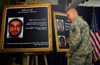 A US solider shows a picture of  Ali Mussa Daqduq (L) 02 July 2007 during a press conference at the heavily fortified Green Zone area in Baghdad.US-led forces arrested an Iranian-controlled Lebanese Hezbollah agent in Iraq, where he was training Iraqi extremists, Bergner told reporters today. Bergner said Ali Mussa Daqduq, also known as Hamid Mohammed Jabur al-Lami, was a senior figure in the Lebanese militant group and had come to Iraq on behalf of Iran's covert Qods Force. AFP PHOTO/POOL/WATHIQ KHUZAIE (Photo by WATHIQ KHUZAIE / POOL / AFP)