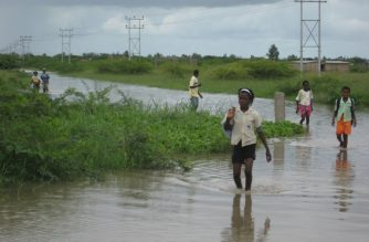 Children returning from school wade through the water covering the street and bridge connecting the suburbs in the outskirts of Chokwe near the Limpopo river on January 26, 2011.  Mozambican emergency services were put on high alert to respond to flooding as water levels rose and thousands abandoned their houses for higher ground. The country's highest decision-making body, the council of ministers, issued a red alert to disaster management workers to be on standby in the event of evacuations or humanitarian need, said government spokesman Alberto Nkutumula.  AFP PHOTO / Johannes Myburgh (Photo by Johannes Myburgh / AFP)