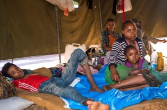 In this photograph taken on August 1, 2018, displaced woman Azaleche Beyene, mother of seven, sits with her children, as they rest at a temporary shelter for Gedeos in Dilla in the Gedeb area of Ethiopia. - Ethiopia's Prime Minister Abiy Ahmed's aggressive reform agenda has won praise, but analysts warn that shaking up Ethiopia's government risks exacerbating several long-simmering ethnic rivalries, such as that between the Oromos and Gedeos. (Photo by Maheder HAILESELASSIE TADESE / AFP)
