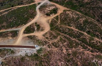 In this aerial view a Border Patrol unit remains next to a section of the US-Mexico border fence as it ends -Mexico on the left side and the United States on the right - at El Nido de las Aguilas, eastern Tijuana, Baja California state on, on March 26, 2019. - A Democrat-led congressional committee challenged Tuesday the Pentagon's plan to divert $1 billion to support President Donald Trump's plan to build a wall on the US-Mexico border. Less than one day after acting Pentagon chief Patrick Shanahan authorized moving the $1 billion from existing Defense Department projects to border construction, the House Armed Services Committee said this move was not permitted. (Photo by Guillermo Arias / AFP)