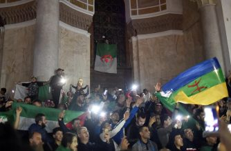 """Algerians celebrate after Algeria's veteran President Abdelaziz Bouteflika informed the Constitutional Council that he is resigning, in Algiers on April 2, 2019. - Bouteflika informed the Constitutional Council he is resigning in a move that is to take effect today, state television said. Bouteflika """"officially advised the Constitutional Council of the end of his term of office as President of the Republic"""" from Tuesday, said a news ticker on the television, shortly after the army chief demanded the immediate launch of impeachment proceedings against the protest-hit leader. (Photo by RYAD KRAMDI / AFP)"""