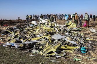 (FILES) In this file photo taken on March 11, 2019 people stand near collected debris at the crash site of Ethiopia Airlines which killed 157 people near Bishoftu, a town some 60 kilometres southeast of Addis Ababa. - Crew of crashed Ethiopian jet 'repeatedly' performed Boeing's recommended procedures,  minister said on April 4, 2019. (Photo by Michael TEWELDE / AFP)