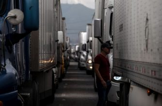 A driver stands next to a cargo truck while lining up to cross to the United States near the US-Mexico border at Otay Mesa crossing port in Tijuana, Baja California state, Mexico, on April 4, 2019. US President Donald Trump is expected to visit a section of the border fence in Calexico during his tour to California on Friday. - US President Donald Trump is expected to visit a section of the border fence in Calexico during his tour to California on Friday. (Photo by Guillermo Arias / AFP)