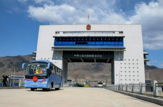 This photo taken on April 8, 2019 shows a tour bus driving past the border between China and North Korea as it makes its way to North Korea, in Ji'an in China's northeastern Jilin province. - The new highway border crossing opened in the northeastern city of Ji'an on April 8, complementing its three existing ports with the North, the city said in a statement published to its website on April 9. (Photo by STR / AFP) / China OUT