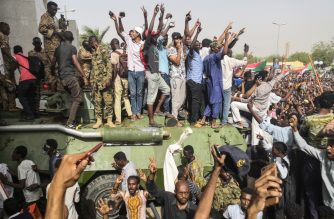 "Sudanese anti-regime demonstrators stand on an army armoured military vehicle on April 11, 2019 as they cheer and flash the sign of victory in the area around the army headquarters where protesters have held an unprecedented sit-in now in its sixth day in Sudan's capital Khartoum to call on their president to step down. - The Sudanese army is planning to make ""an important announcement"", state media said today, after months of protests demanding the resignation of longtime leader President Omar al-Bashir. Thousands of Khartoum residents chanted ""the regime has fallen"" as they flooded the area around the military headquarters. (Photo by - / AFP)"