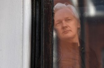 (FILES) In this file photo taken on May 19, 2017 Wikileaks founder Julian Assange look out from a window at the Embassy of Ecuador in London. - British police have arrested WikiLeaks founder Julian Assange at Ecuador's embassy in London after his asylum was withdrawn, the police said in a statement on April 11, 2019. (Photo by Justin TALLIS / AFP)