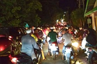 This photograph taken with a phone shows Indonesian residents rushing for higher ground fearing a tsunami after a strong 6.8 magnitude earthquake rocked Luwuk, in Central Sulawesi of eastern Indonesia on April 12, 2019. - A strong 6.8 magnitude earthquake rocked eastern Indonesia on April 12, the United States Geological Survey said, triggering a tsunami warning and sending panicked residents fleeing from their homes. (Photo by STR / AFP)