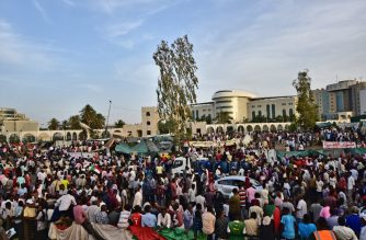 "Sudanese demonstrators gather near the military headquarters in the capital Khartoum on April 14, 2019. - Sudanese protesters today demanded the country's military rulers ""immediately"" hand power over to a civilian government that should then bring ousted leader Omar al-Bashir to justice. (Photo by Ahmed MUSTAFA / AFP)"