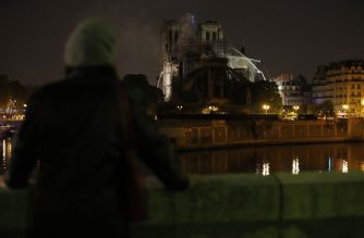 Bystanders look on as flames and smoke billow from the roof at Notre-Dame Cathedral in Paris early on April 16, 2019. - A major fire broke out at the landmark Notre-Dame Cathedral in central Paris sending flames and huge clouds of grey smoke billowing into the sky, the fire service said. The flames and smoke plumed from the spire and roof of the gothic cathedral, visited by millions of people a year, where renovations are currently underway. (Photo by Zakaria ABDELKAFI / AFP)