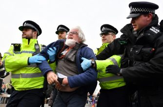 "British police officers arrest an activist as they remove them from their blockade of Waterloo Bridge on the second day of an environmental protest by the Extinction Rebellion group, in London on April 16, 2019. - Environmental protesters from the Extinction Rebellion campaign group started a programme of demonstrations designed to block five of London's busiest and iconic locations to draw attention to what they see as the ""Ecological and Climate Emergency"" of climate change. (Photo by Ben STANSALL / AFP)"
