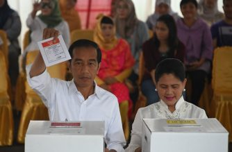 Incumbent President Joko Widodo (L) and his spouse Iriana Widodo (R) cast their ballot at a polling center during the presidential and legislative election in Jakarta on April 17, 2019. - Indonesia's heavy metal-loving leader Joko Widodo faces off against ex-military general Prabowo Subianto in the race to lead the world's third-biggest democracy, a re-run of the 2014 election contest narrowly won by Widodo. (Photo by BAY ISMOYO / AFP)