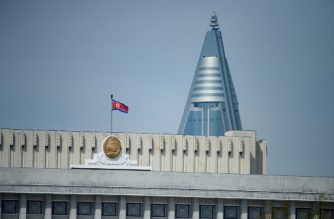 In a photo taken on April 16, 2019 a North Korean flag flies above the Supreme People's Assembly in Pyongyang. (Photo by Ed JONES / AFP)