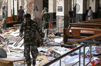 Sri Lankan security personnel walk past dead bodies covered with blankets amid blast debris at St. Anthony's Shrine following an explosion in the church in Kochchikade in Colombo on April 21, 2019. - A string of blasts ripped through high-end hotels and churches holding Easter services in Sri Lanka on April 21, killing at least 156 people, including 35 foreigners. (Photo by ISHARA S.  KODIKARA / AFP)