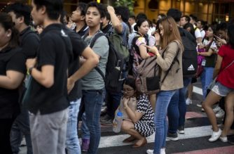 Employees are seen at an open area in Manila, after an earthquake rocked the Philippines on April 22, 2019. - A powerful earthquake rocked the Philippines, sending thousands of people fleeing high-rises in Manila as buildings shook. Office workers piled out onto the streets as emergency alarms blared, AFP reporters saw, but there were no immediate reports of injuries or damage. (Photo by Noel CELIS / AFP)