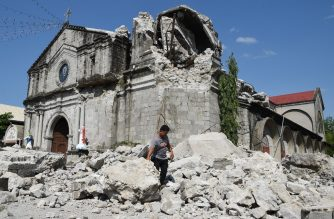 A church worker walks past rubble of the 18th century St. Catherine of Alexandria after its bell tower was destroyed following a 6.3 magnitude earthquake that struck the town of Porac, pampanga province on April 23, 2019. - Philippine rescuers were scrambling April 23 to reach dozens of people feared buried under a building near Manila that collapsed a day earlier in a powerful earthquake, as the death toll climbed to 11. (Photo by TED ALJIBE / AFP)