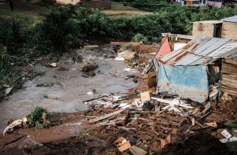 People abandon their homes after they were destroyed by torrential rains and flash floods at an informal settlement of BottleBrush, south of Durban, on April 23, 2019. - The death toll from floods and mudslides that crushed homes in the South African port of Durban on April 23 has risen to 33, with reports of children missing and scores of people displaced, authorities said. (Photo by RAJESH JANTILAL / AFP)