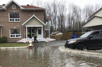 Firefighters check on people in their homes in preparation for increased flooding in Gatineau, Quebec on April 24, 2019. - Flooding in eastern Canada forced the evacuation of more than 1,500 people over the past weekend while over 600 troops have been deployed in response, authorities said. (Photo by Michel COMTE / AFP)