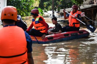 A rescue team evacuates a resident from a flooded neighborhood in Jakarta, on April 26, 2019, after several areas were affected by heavy rainfall. (Photo by BAY ISMOYO / AFP)