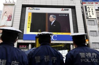 "Japanese policemen stand guard as they look at a screen displaying live news of Japanese Emperor Akihito's abdication ceremony in Tokyo on April 30, 2019. - Akihito is handing over the Chrysanthemum Throne to his eldest son, 59-year-old Crown Prince Naruhito, in a series of solemn rituals that also usher in the new imperial era named ""Reiwa"" -- meaning beautiful harmony -- that will last throughout the new monarch's reign. (Photo by Toshifumi KITAMURA / AFP)"