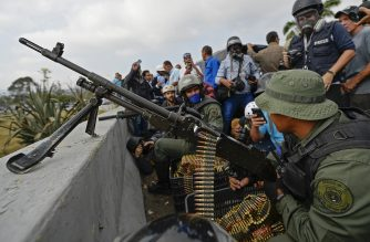 Members of the Venezuelan Armed Forces supporting Venezuelan opposition leader and self-proclaimed acting president Juan Guaido take position in front of La Carlota base in Caracas on April 30, 2019. - Guaido said on Tuesday that troops had joined his campaign to oust President Nicolas Maduro as the government vowed to put down what it called an attempted coup. (Photo by Matias DELACROIX / AFP)