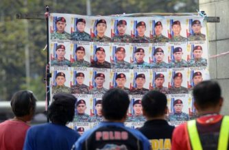People look at a display of photos in Manila on February 7, 2015 showing the 44 elite commandos who died in a police raid in Mamasapano town, in the southern island of Mindanao during a mission in January to capture one of the world's most wanted terrorists, Bali bomber Zulkifli bin Hir. The hunt for Zulkifli ended at his hideout on remote farmland in the southern island of Mindanao just before dawn on January 25. Philippines media on February 6 ran a photo purportedly showing his dead body, sprawled in a hut and in a blood-soaked shirt. Philippine Muslim rebels said they were considering returning dozens of high-powered firearms that they seized from some of the 44 police commandos killed in a botched anti-terror operation in the south.   AFP PHOTO / Jay DIRECTO (Photo by JAY DIRECTO / AFP)