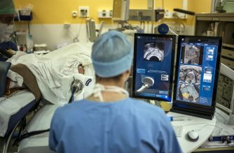 A surgeon sitting in front of screens of a Focal Onedevice performs a robot-assisted prostate tumorectomy using ultrasound imaging on April 10, 2014 at the Edouard Herriot hospital in Lyon, center France. Focal One is the first robotic HIFU (high intensity focused ultrasound) device dedicated to the focal approach for prostate cancer therapy. According to EDAP TMS SA, a leader in therapeutic ultrasound, it combines the three essential components to efficiently perform a focal treatment: state-of-the-art imaging to localized tumors with the use of magnetic resonance imaging (MRI) combined with real-time ultrasound, utmost precision of robotic HIFU treatment focused only on identified targeted cancer areas, and immediate feedback on treatment efficacy utilizing Contrast-Enhanced Ultrasound Imaging. AFP PHOTO / JEFF PACHOUD (Photo by JEFF PACHOUD / AFP)