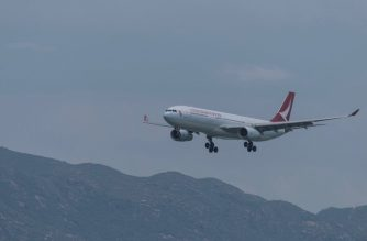 A Cathay Dragon passenger plane makes its descent before landing at Hong Kong's international airport on August 16, 2017. - The city's flagship airline Cathay Pacific was expected to announce its half-year results later in the day. (Photo by Anthony WALLACE / AFP)